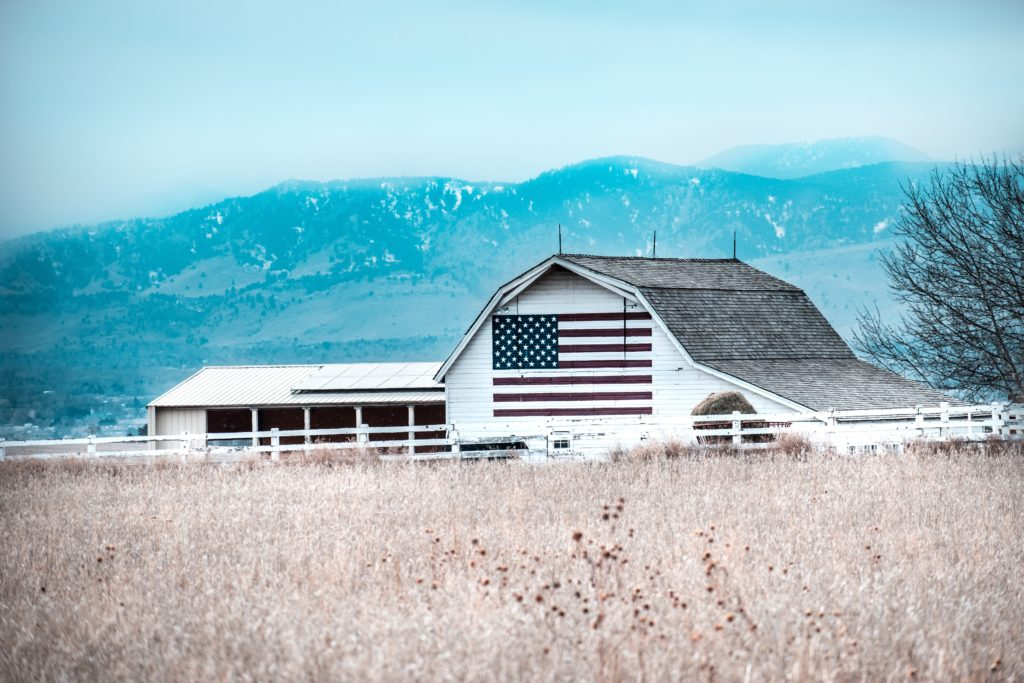 white barn with painted American flag in field with blue sky