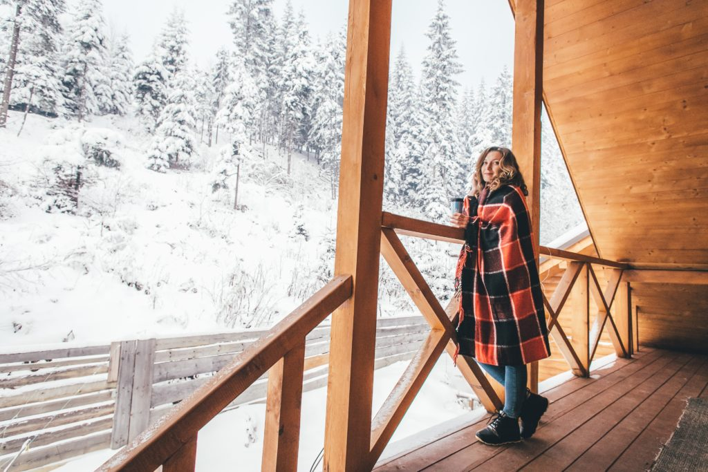 woman standing on pole barn porch in winter