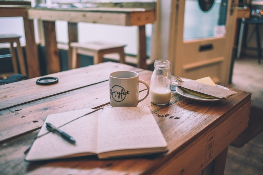 coffee cup and journal on wooden table