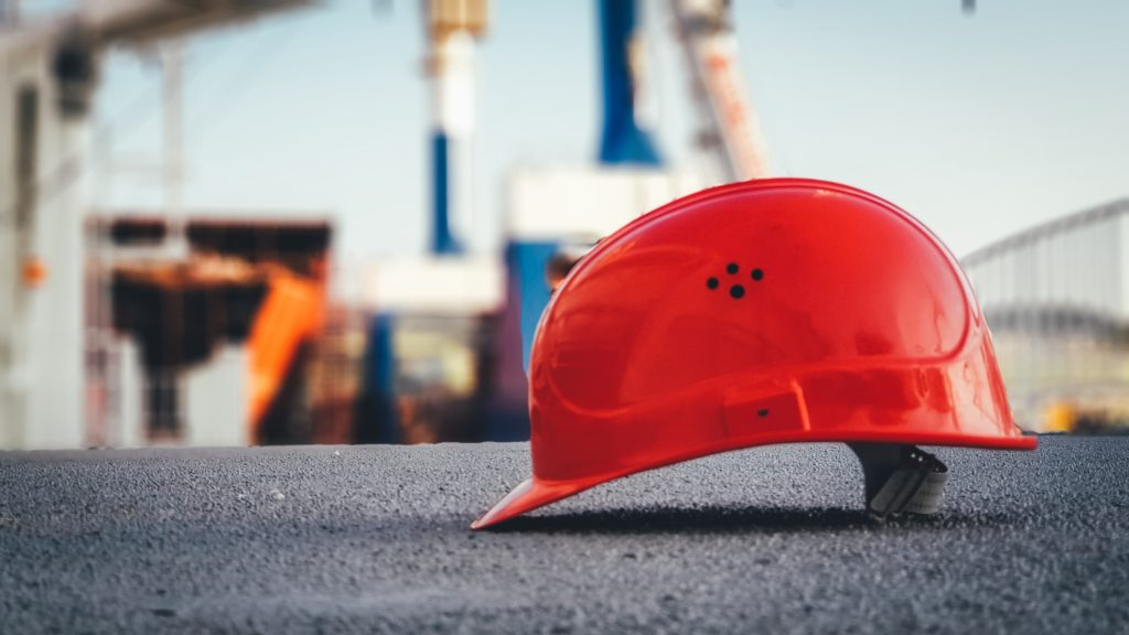 red construction worker hat on concrete